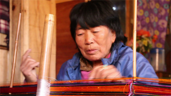 74 years old women weaving for her grand childrens.